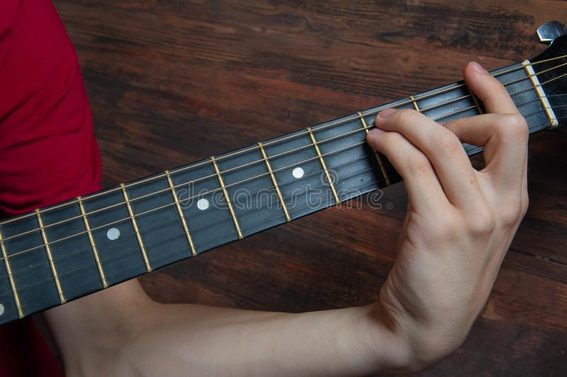 Hand of man playing six-string guitar on wooden background. Template for concert poster royalty free stock photo