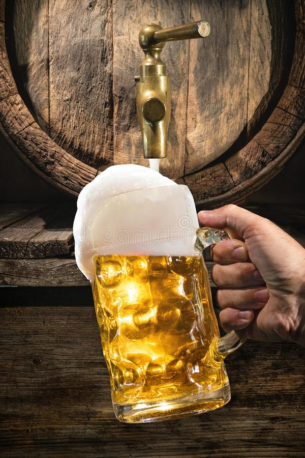 Hand of man is pouring a large lager beer in tap from wooden beer barrel. Background for Oktoberfest, folk or beer festival stock photography