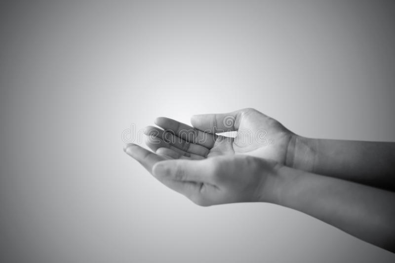 Hand of man praying and asking. In white and black stock photo
