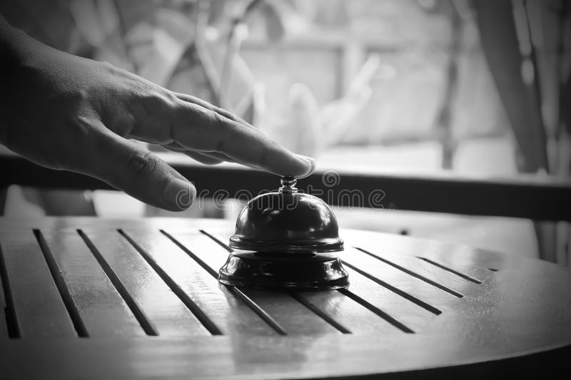 Hand man push hotel bell black and white. stock photo