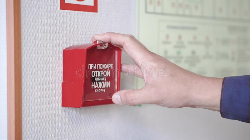The hand of man is pushing fire alarm on the wall. Clip. Hand of man pushing fire alarm switch on the white wall as royalty free stock photo
