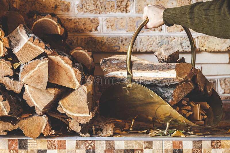 Hand man raises woodpile with logs. Hand of man holding curved handle copper woodpile filled with firewood. Nearby on a shelf stacked logs stock image