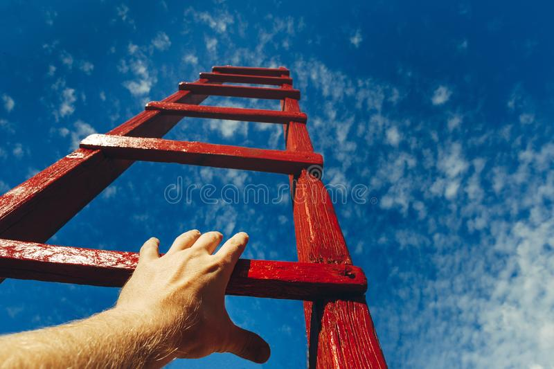 Hand Of Man Reaching For Red Ladder Leading To A Blue Sky. Development motivation Career Growth Concept. A male hand holds onto the crossbar of a red wooden stock photo