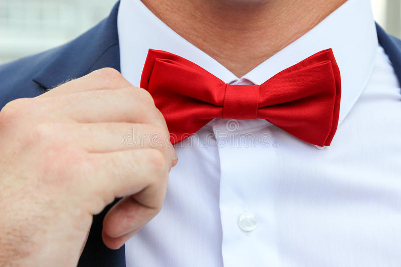 Hand of man readjusting red bow tie, close-up photo. royalty free stock photo