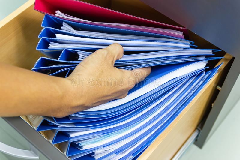 Hand of Man Search files document in a file cabinet in work office royalty free stock photo