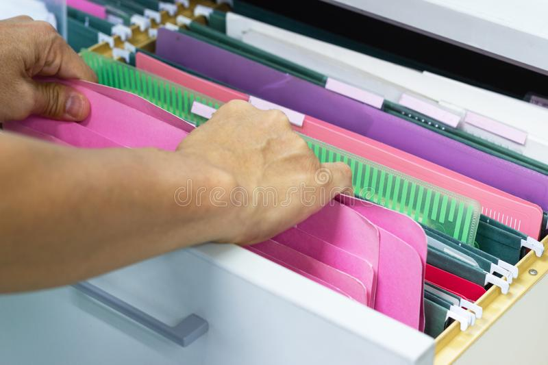 Hand of Man search files document of hanging file folders in a drawer in a whole pile of full papers. At work office Bangkok Thailand Business Concept stock photo