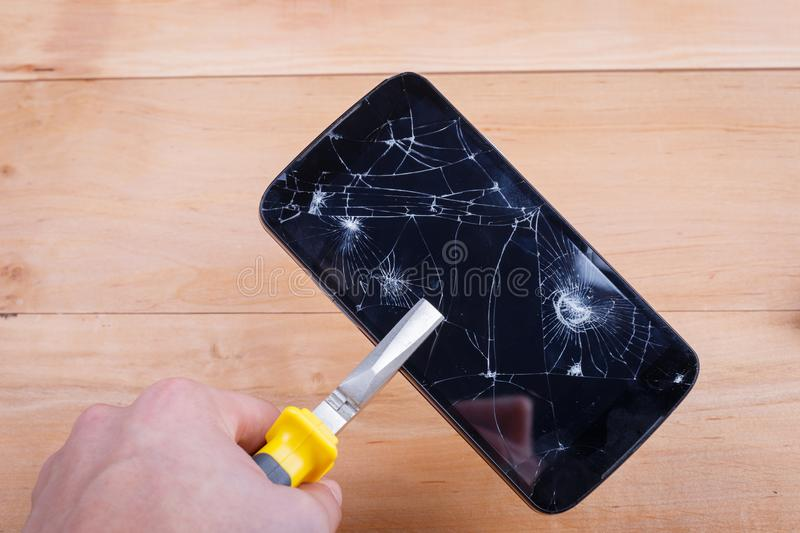 The hand of the man, squeezed by pliers mobile phone with a broken screen. royalty free stock images