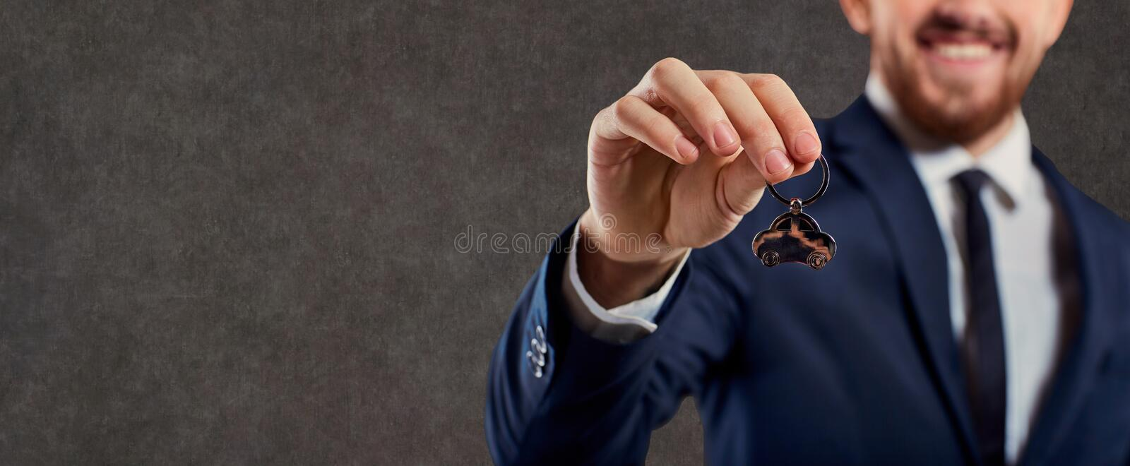 Hand of a man in a suit with a keychain for a car key. Hand of a man in a suit with a keychain for a car key against a copyspace background royalty free stock photo