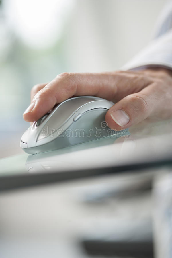 Hand of man using his forefinger to control a cordless mouse royalty free stock images