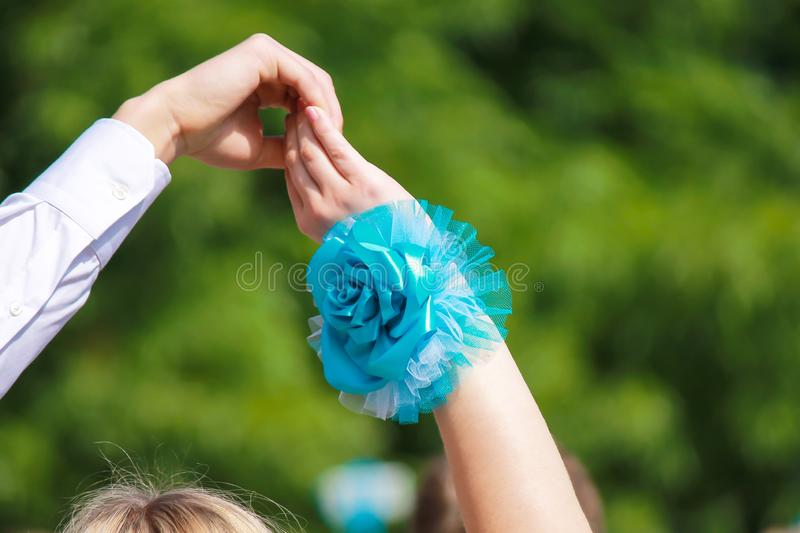 The hand of a man in a white shirt and a woman with a blue flower raised up on a green background. Festive, wedding, birthday stock image
