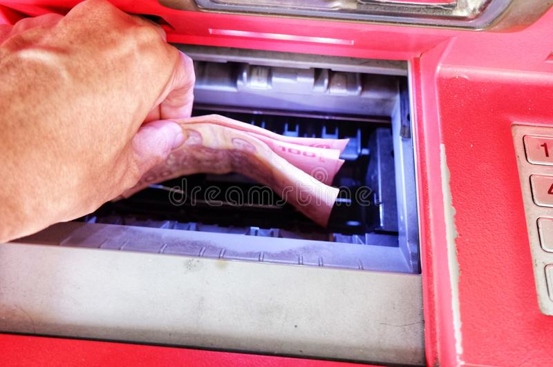 A man is withdraw money from ATM. stock photos