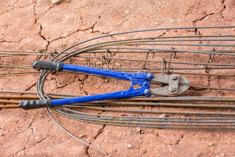 Hand manual steel wire rope cutter, Shear cutter, Bolt cutter an. D steel bar put on soil stock photos