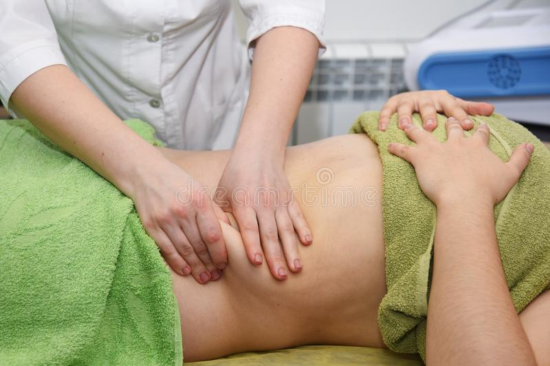 Hand massage of the abdomen. Body care. Non surgical body sculpting. Anti-cellulite and anti-fat therapy in beauty salon. Hand massage of the abdomen. Body care royalty free stock images