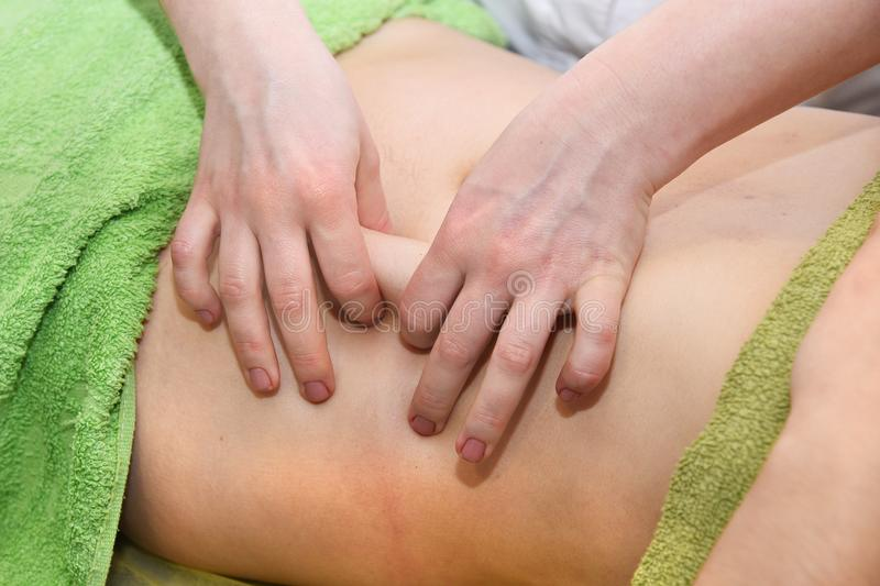 Hand massage of the abdomen. Body care. Non surgical body sculpting. Anti-cellulite and anti-fat therapy in beauty salon. Hand massage of the abdomen. Body care stock images