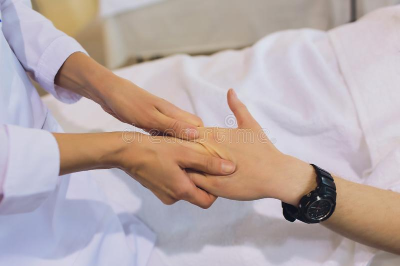 Hand massage. Physiotherapist pressing specific spots on female palm. Professional health and wellness acupressure stock image