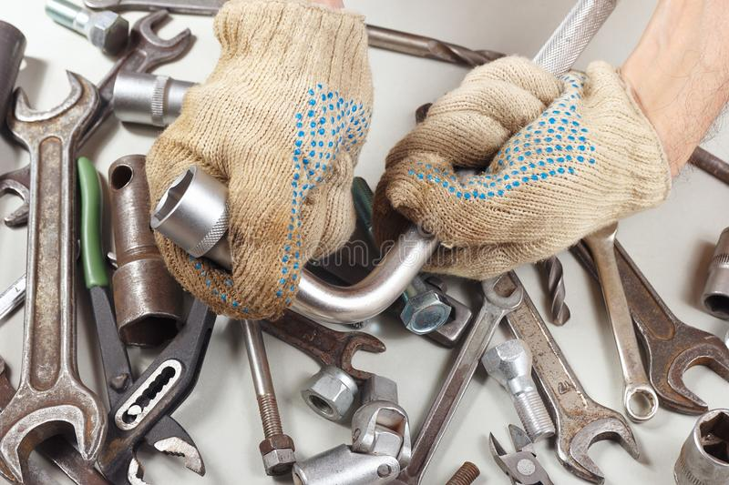 Hand of master in gloves with tools for repairing machines in workshop stock photos