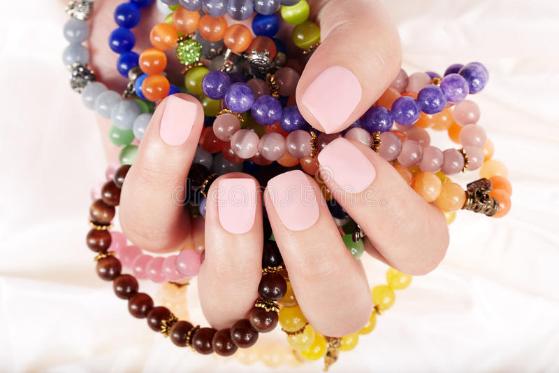 Hand with matte manicured nails and colorful bracelets stock image