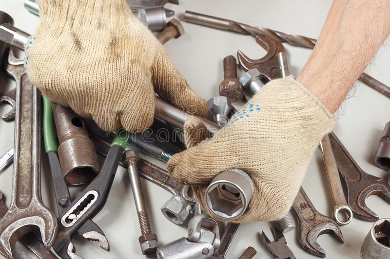 Hand of mechanic in gloves with tools for repairing machines in workshop stock image