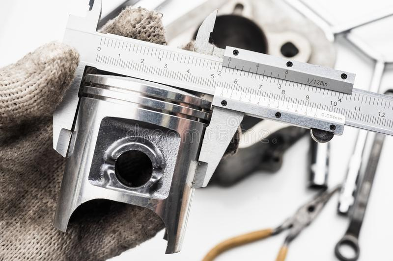 Hand of mechanic holding Vernier Caliper Measurements on The mot. Orcycle Piston royalty free stock images