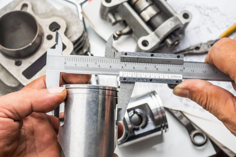 Hand of mechanic holding Vernier Caliper Measurements on The mot. Orcycle Piston stock photos