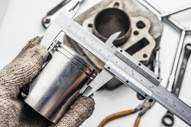 Hand of mechanic holding Vernier Caliper Measurements on The mot. Orcycle Piston royalty free stock image