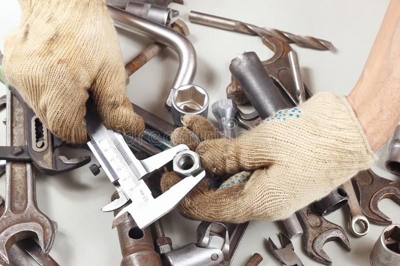 Hand of mechanic measure the nut with calliper in the workshop stock photography