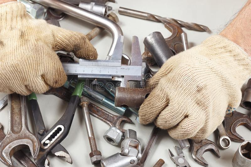 Hand of mechanic measure the part with a calliper in workshop royalty free stock photo