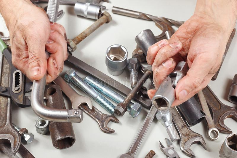 Hand of mechanic repairing parts of the mechanism in workshop royalty free stock photography