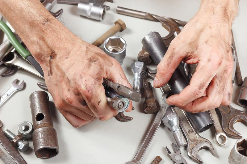 Hand of mechanic with tools for repairing machines in workshop stock photography