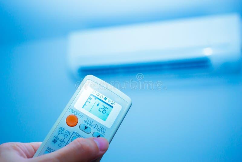 Hand med den avlägsna luftkonditioneringsapparaten royaltyfria bilder