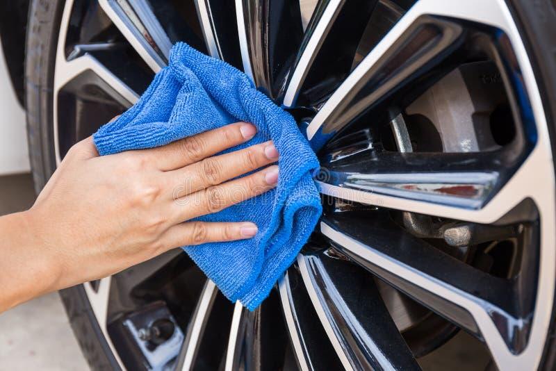 Hand med den blåa bilen för microfibertorkdukelokalvård royaltyfri fotografi