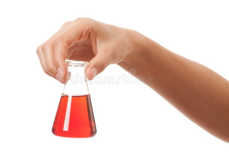 Hand med den kemiska flaskan som isoleras på vit royaltyfri foto
