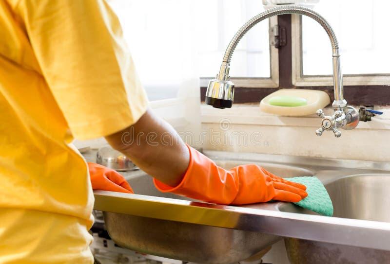 Hand med den orange handskelokalvårddiskhon arkivfoto