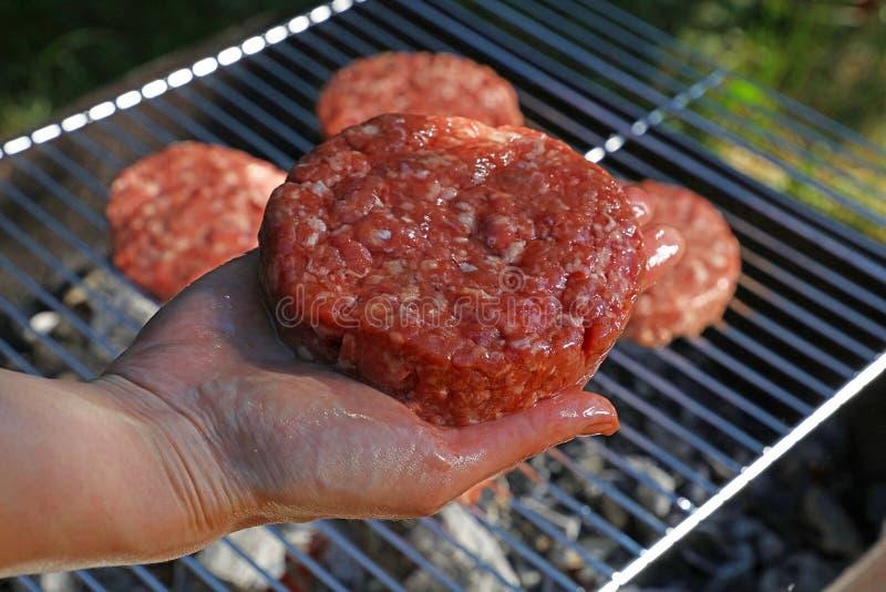 Hand med den rå nötkötthamburgaren för hamburgare royaltyfria foton