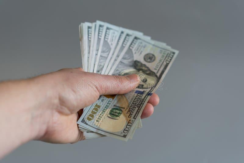 Hand med dollar på en grå bakgrund Dollar pengarfinansvaluta i hand på grå bakgrund Vertikalt foto royaltyfria foton