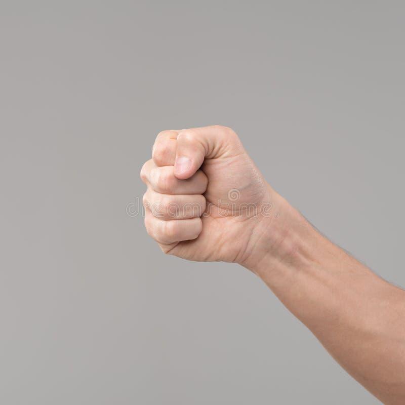 Hand med en isolerad gripen hårt om näve arkivfoton