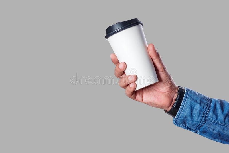 Hand med en kopp på grå bakgrund fotografering för bildbyråer
