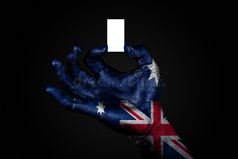 Hand med en målad flagga Australien som rymmer ett litet vitt ark med utrymme för en inskrift som är falskt upp royaltyfri illustrationer