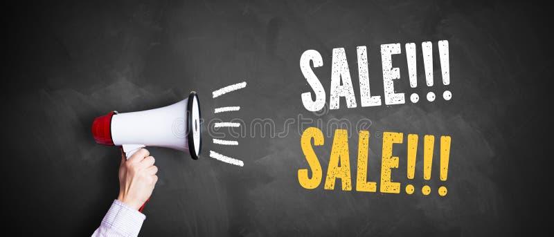 Hand med en megafon som är främst av en svart tavla med meddelande`en Sale!!! Sale!!! `, royaltyfria bilder