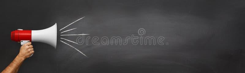 Hand med en megafon som är främst av en tom svart tavla arkivbilder