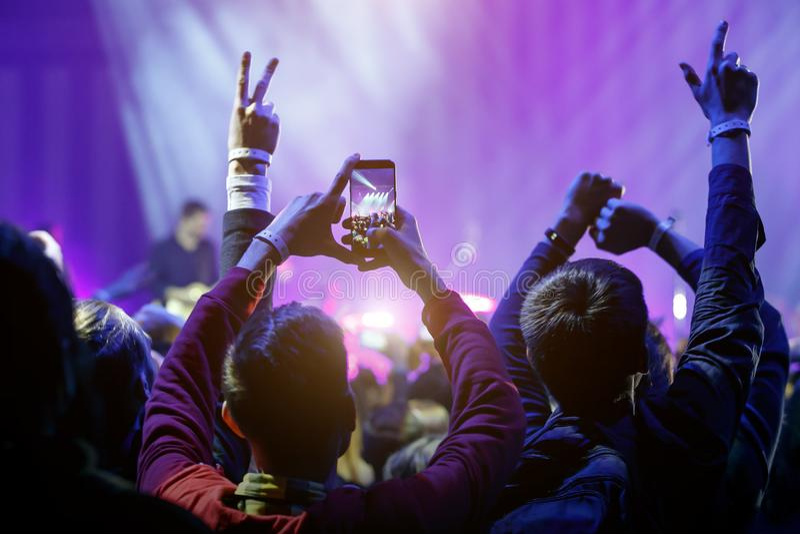 Hand med en smartphone på konserten för levande musik som tar fotoet av etappen som är levande, musikfestival arkivfoton