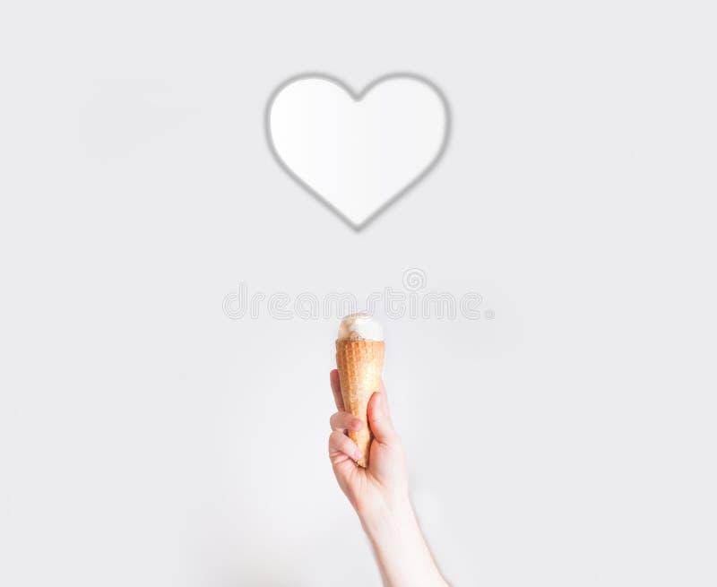 Hand med glass på bakgrund av hjärtor, begrepp av 8 mars, royaltyfri bild