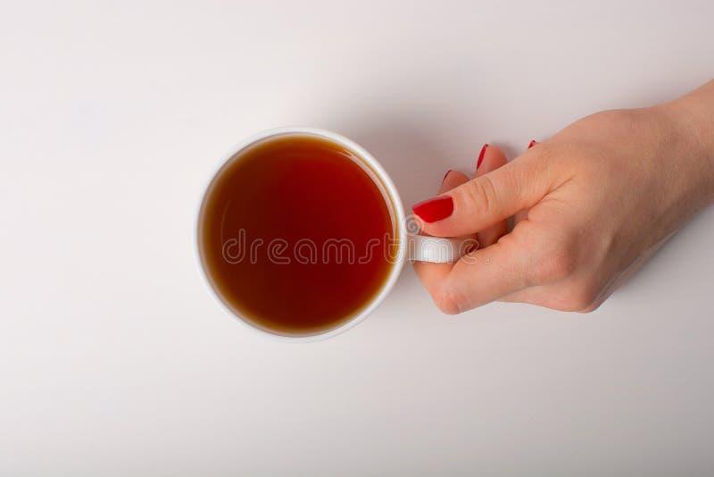 Hand med koppen av tea royaltyfria foton