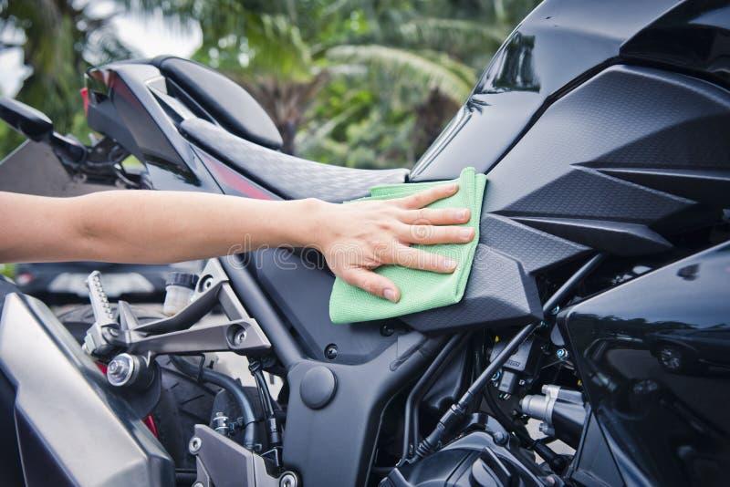 Hand med lokalvårdmotorcykeln royaltyfri bild