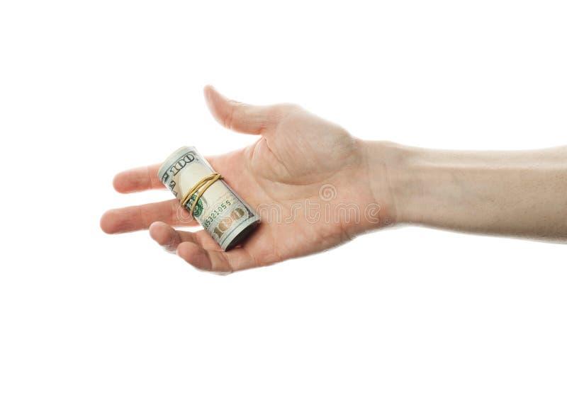 Hand med pengar som vi dollar rullar isolerat på en vit bakgrund arkivbild