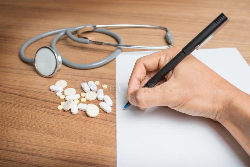 Hand med pennan över form för tomt papper med stetoskopet och preventivpillerar fotografering för bildbyråer