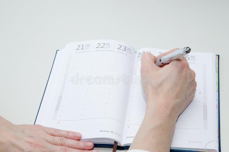 Hand med pennan och dagboken arkivbilder