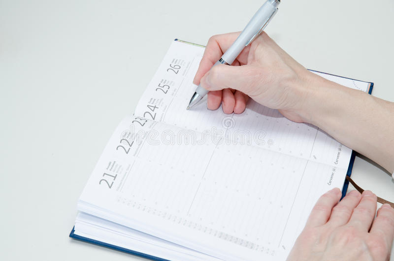 Hand med pennan och dagboken royaltyfri foto