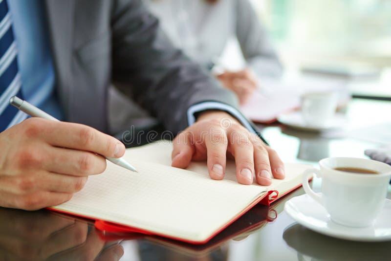 Hand med pennan och notepaden royaltyfria foton