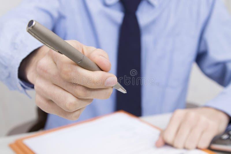 Hand med pennan som ska undertecknas arkivbilder